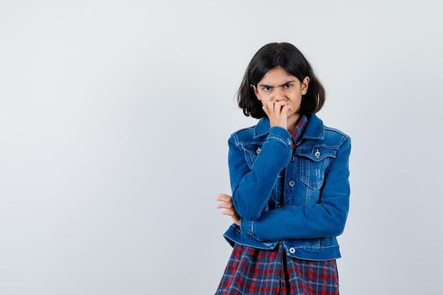 Bambina che tiene la mano sulla bocca in camicia, giacca e sembra pensierosa, vista frontale.