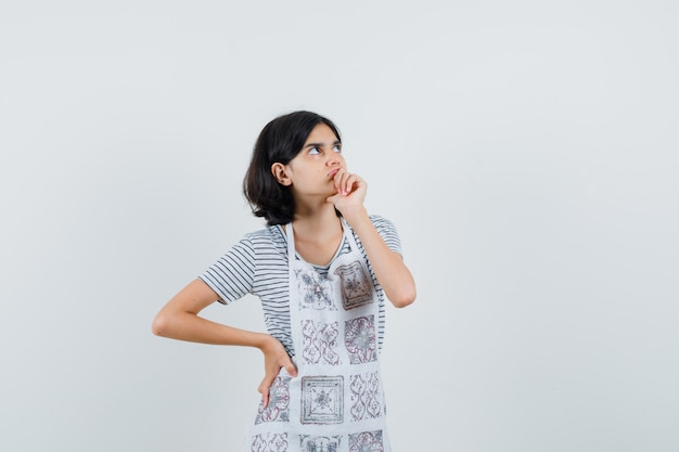 Bambina tenendo la mano sulla bocca in t-shirt, grembiule e guardando esitante,