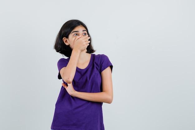 Bambina che tiene la mano sulla bocca in maglietta e che sembra sorpreso.