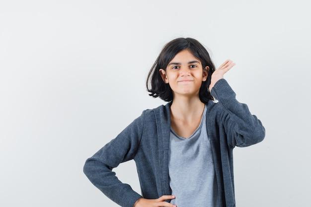 Bambina che tiene la mano vicino all'orecchio in maglietta, giacca e sembra allegra. vista frontale.