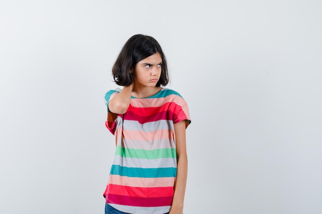 Little girl holding hand on neck, looking away in t-shirt and looking displeased , front view.
