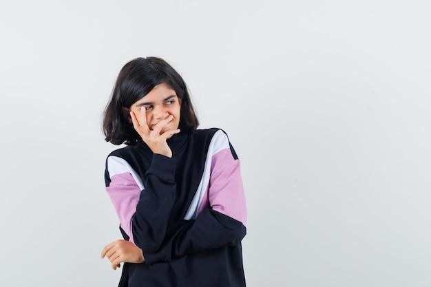 シャツの頬に手をつないで、楽観的な正面図を探している少女。