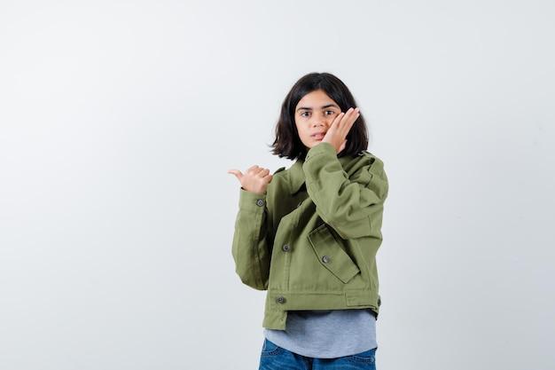 小さな女の子が頬に手をつないで、コート、tシャツ、ジーンズの親指で脇を指して、驚いて見える、正面図。