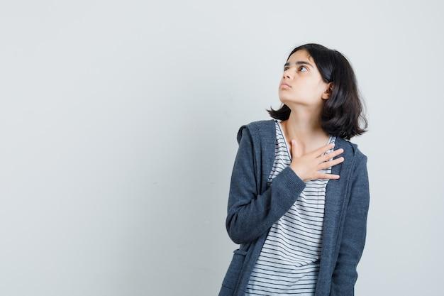 Маленькая девочка держит руку на груди в футболке, куртке и выглядит испуганной.