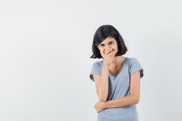 Tシャツのあごに手をつないで夢のように見える少女。正面図。