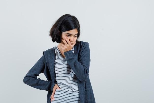 Tシャツ、ジャケットのあごに手をつないで、無力に見える少女。