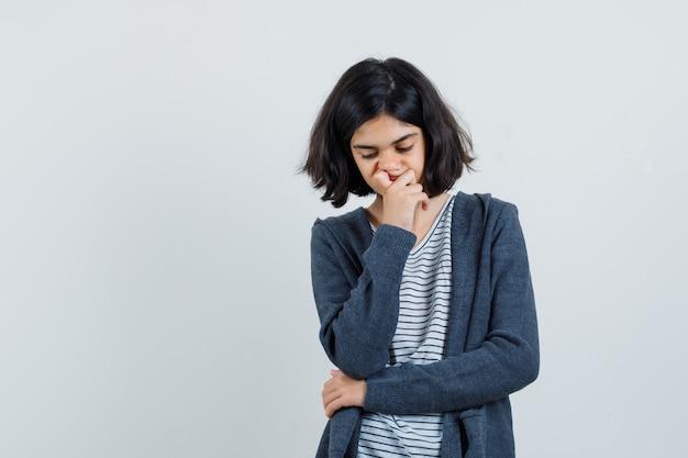 Tシャツ、ジャケット、物思いにふけるあごに手をつないでいる少女、