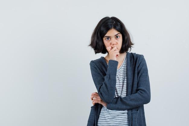 Tシャツ、ジャケット、思慮深く見えるあごに手をつないでいる少女、