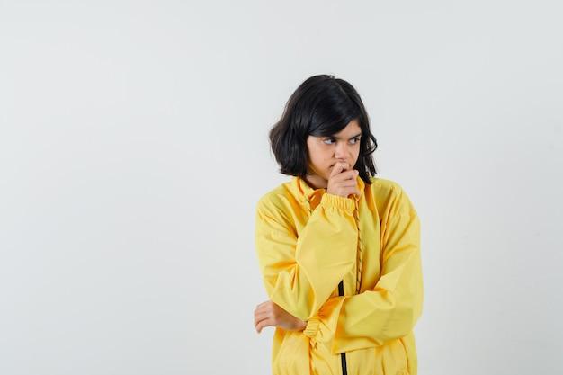 黄色いパーカーのあごに手をつないで、思慮深く、正面図を探している少女。