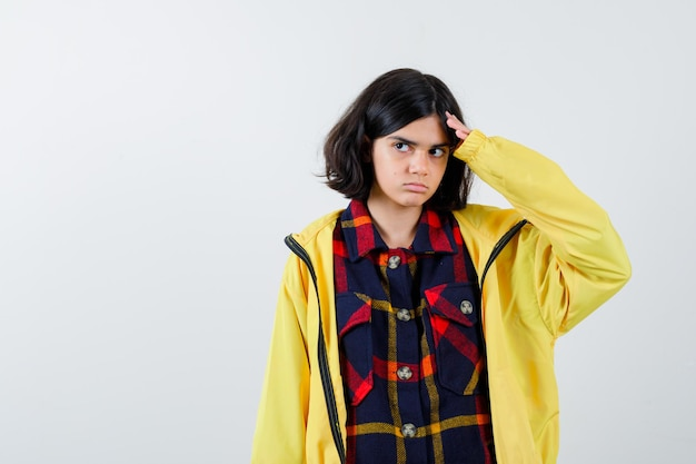 Маленькая девочка держит руку на голове в клетчатой рубашке, куртке и выглядит нерешительно. передний план.
