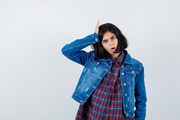 シャツ、ジャケットで頭に手をつないで、後悔している少女。正面図。