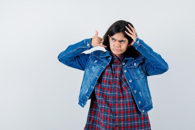 頭に手をつないで、シャツ、ジャケットで電話のジェスチャーを示し、暗い、正面図を探している少女。