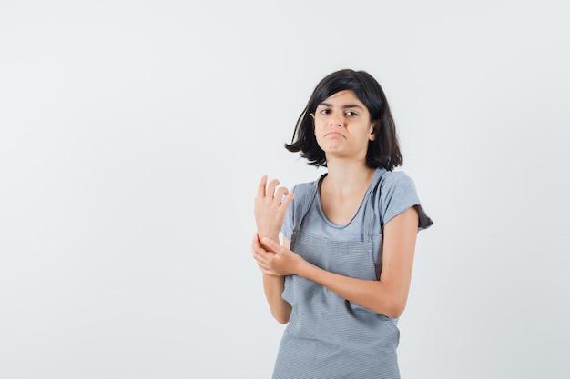 Tシャツ、エプロン、混乱しているように見える、正面図で彼女の手首に手をつないでいる少女。