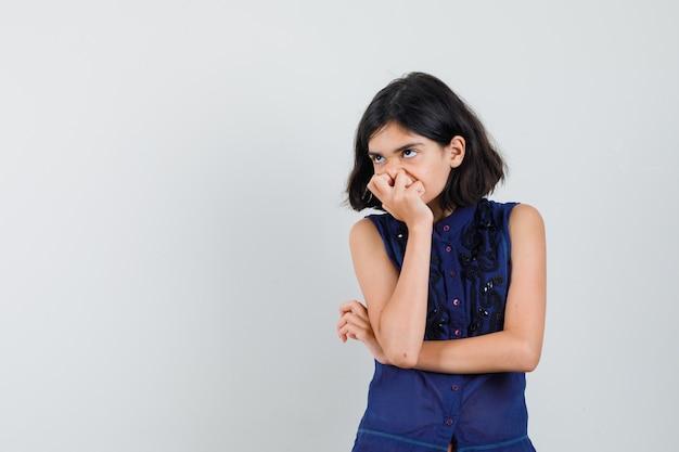 青いブラウスで口に手をつないで物思いにふける少女。正面図。