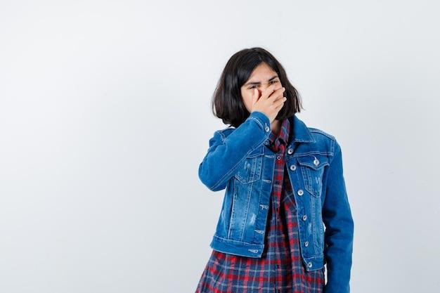 シャツ、ジャケットで口に手をつないで、悲しそうに見える少女。正面図。