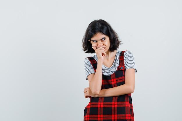 T- 셔츠, 점프 슈트에서 멀리보고 복잡 하 게 보이는 동안 입에 손을 잡고 어린 소녀.
