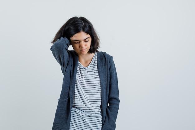 Маленькая девочка держит руку на шее в футболке, куртке и выглядит задумчивой,