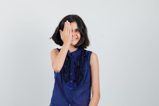 青いブラウスで片方の目に手をつないで、陽気に見える少女、正面図。
