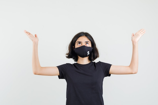 Little girl holding hands as raising something in black t-shirt, mask , front view.