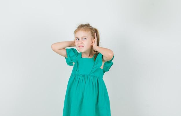 Bambina che tiene le mani dietro le orecchie in vestito verde e che sembra scontento. vista frontale.
