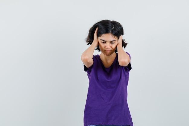 Bambina che tiene le mani sulle orecchie in maglietta e guardando infastidito,