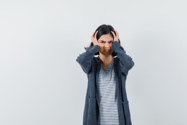 Bambina che tiene le mani sulla testa in t-shirt, giacca e guardando ansioso,