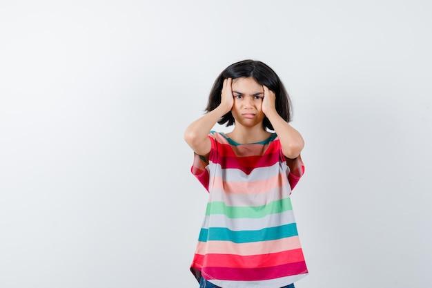 Bambina che si tiene per mano sulla testa in maglietta e sembra dispiaciuta. vista frontale.
