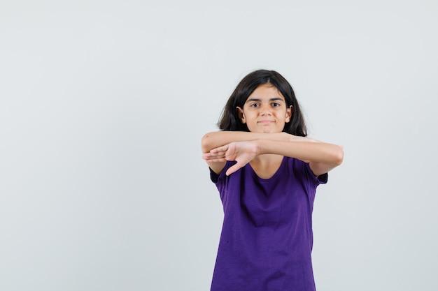 Маленькая девочка держит руки в воздухе в футболке и выглядит уверенно,