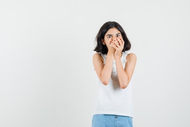 Bambina che tiene le mani sulla bocca in camicetta bianca, pantaloncini e sembra spaventata, vista frontale.