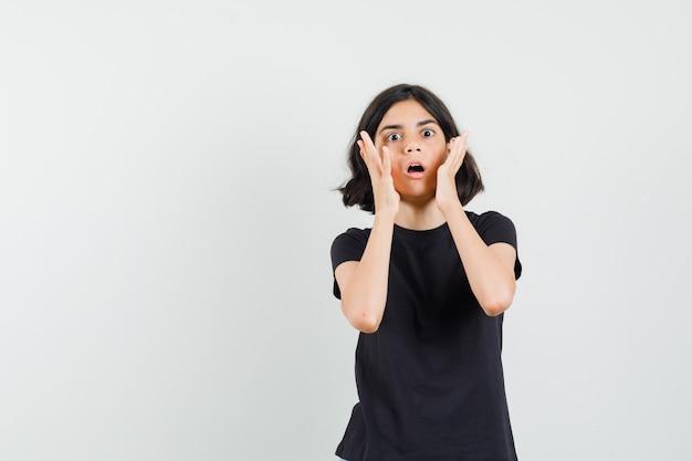Bambina che tiene le mani vicino alla bocca aperta in maglietta nera e che sembra spaventata, vista frontale.