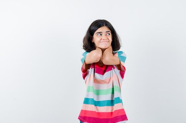 Bambina che si tiene per mano sul collo, distogliendo lo sguardo in t-shirt, jeans e guardando felice, vista frontale.