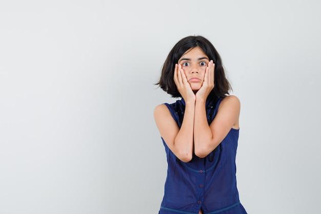 Маленькая девочка, держась за щеки в синей блузке и потрясенная, вид спереди.