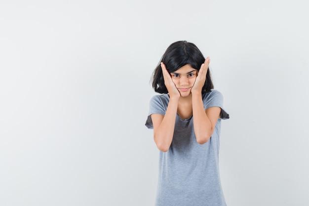 Tシャツの頬に手をつないで混乱しているように見える少女。正面図。
