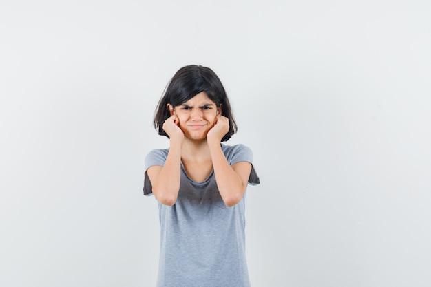 Tシャツを着て頬に手をつないで気分を害している少女。正面図。