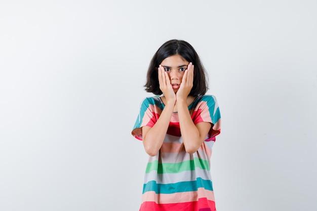 어린 소녀는 티셔츠, 청바지를 입은 뺨에 손을 잡고 놀란 표정을 짓고 있습니다. 전면보기.