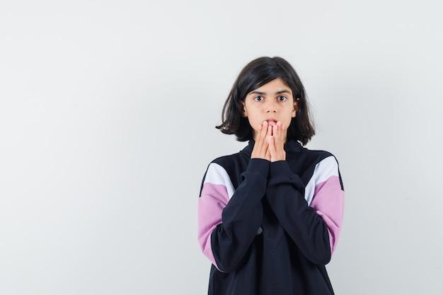 シャツのあごに手をつないで、不安そうな正面図を探している少女。