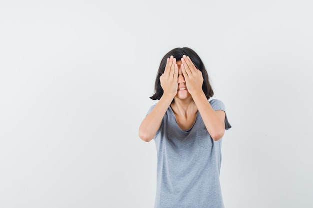 어린 소녀 t- 셔츠에 눈에 손을 잡고 흥분 찾고. 전면보기.