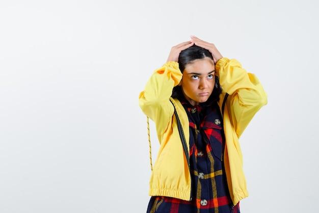チェックのシャツ、ジャケットで頭に手をつないで、忘れて見える少女。正面図。