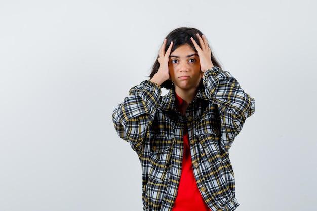 Маленькая девочка, взявшись за голову в рубашке, куртке, вид спереди.