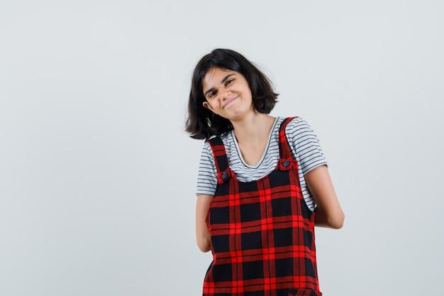 Маленькая девочка держит руки на спине в футболке, комбинезоне и выглядит радостной,