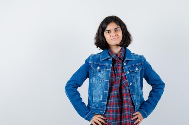シャツ、ジャケット、自信を持って腰に手をつないでいる少女。正面図。