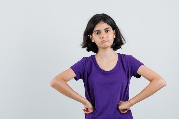 T- 셔츠에 허리에 손을 잡고 혼란 스 러 워 보이는 어린 소녀.