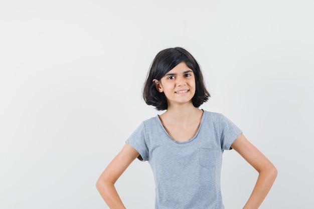 Маленькая девочка держит руки на талии в футболке и выглядит оптимистично. передний план.