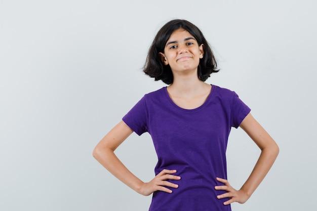 T- 셔츠에 허리에 손을 잡고 낙관적 찾고 어린 소녀.