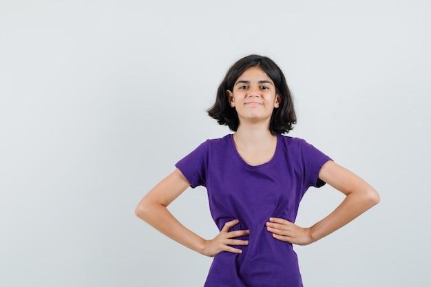 어린 소녀는 t- 셔츠에 허리에 손을 잡고 자랑스럽게보고,