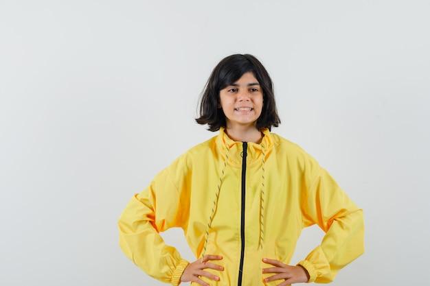 Маленькая девочка держит руки на талии в желтой толстовке с капюшоном и выглядит мечтательно. передний план.