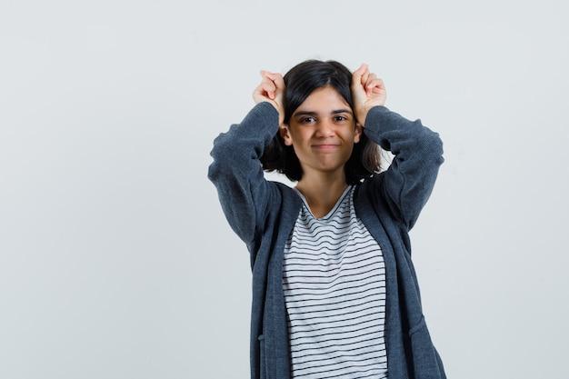 Маленькая девочка держит руки над головой как уши в футболке, куртке и выглядит смешно,