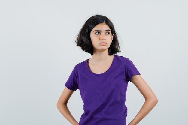 Bambina che tiene le mani sulla vita in maglietta e sembra triste.