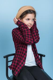 Little girl holding hat on head