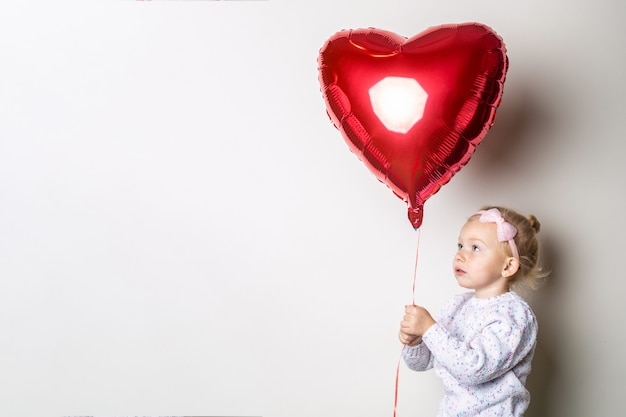 Little girl holding a heart air balloon on a light background. concept for valentine's day, birthday. banner.